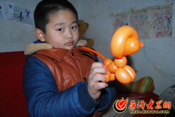 吹气球不仅是力气活,还需要拿捏吹气的力度,吹多大多长?需要按吹的造型来定。而每次做东西,小正一都了然于胸。  小正一展示刚刚做好的贵宾犬造型,栩栩如生,生动可爱,这个只需花1分钟时间就能做好。  为了让小正一玩得开心,妈妈还给他买了配套材料,这只天鹅加上两只眼睛后,更加逼真了。  小正一的成熟、淡定给大众网记者带来一种错觉,在妈妈喂他吃东西的片刻,才想起来他其实还是个孩子。  一小会功夫,小正一就做出了一堆造型,其中还不乏一个小熊抱心的高难度作品。 大众网菏泽1月8日讯(记者 郭 豪)一只普通的长气球