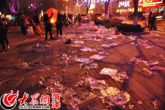 满地的透明垃圾袋  地上还有许多未成功放飞的孔明灯残骸 2月14日晚,元宵佳节之际,牡丹广场人山人海,许多市民纷纷放起了孔明灯。而包装孔明灯的透明塑料袋,则被市民随手丢弃在广场,现场一片狼藉。据记者粗略统计,丢弃在地上的垃圾袋逾万只。 大众网记者 钟博陵 见习记者 付娜 摄