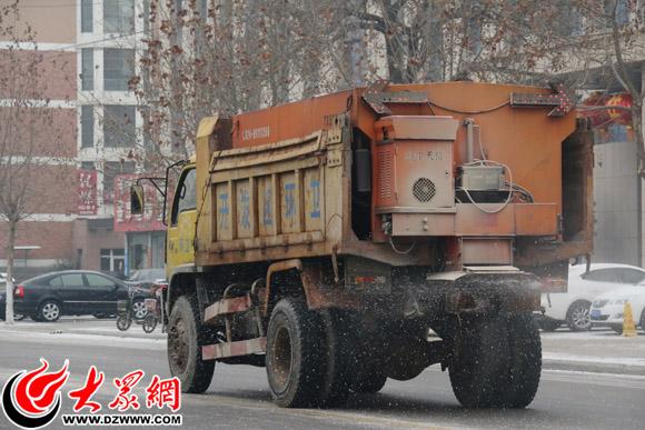 城区路面上的撒盐车-菏泽城区一天扫三遍 扫雪车带走一片风雪留下一图片