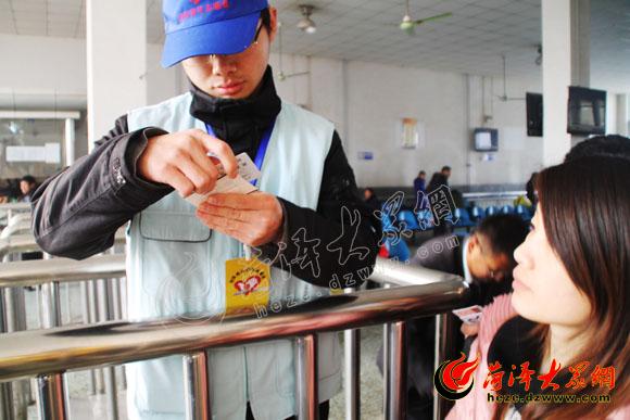 春运服务志愿者赵斌核对车票和身份证信息