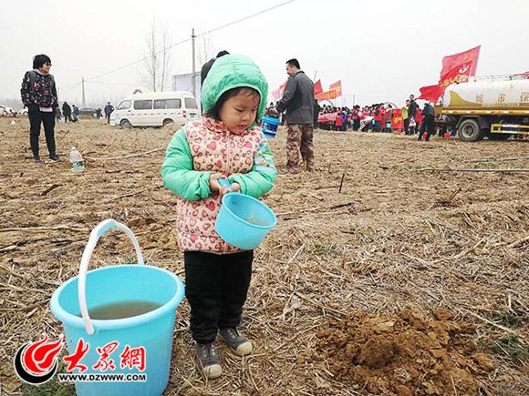 参与植树的小朋友在给树木浇水